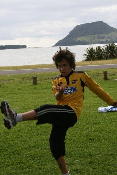 Sam kicks rugby ball in park